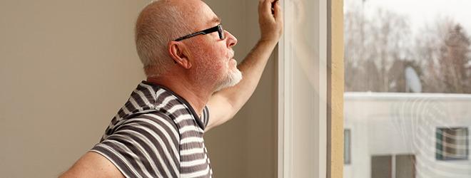 Mann mit Fibromyalgie blickt aus Fenster