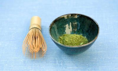 Matcha-Pulver wird mit einem Bambuswedel in heißes Wasser gerührt.
