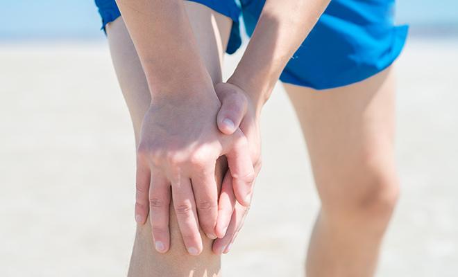 Mann fasst sich an Kniegelenk mit Arthrose
