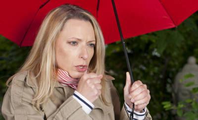 Hartnäckiger Husten: eine Frau steht hustend unter einem roten Regenschirm.
