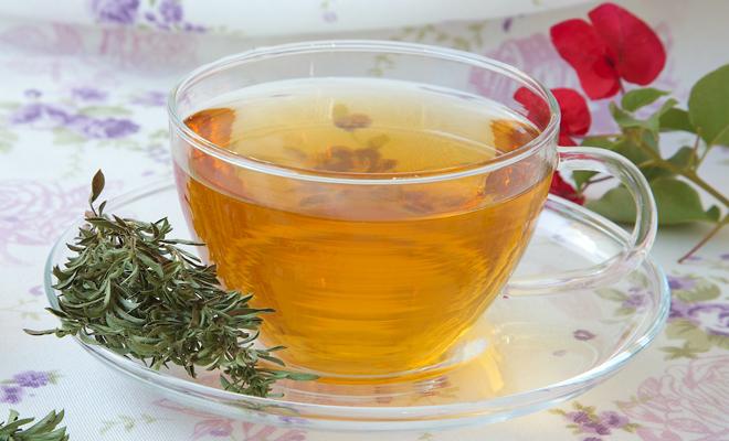 Husten: Teetasse mit Tee, an der Seite liegt frischer Thymian