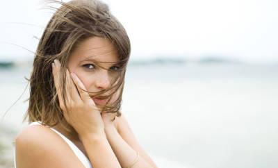 Eine junge Frau mit Ohrenschmerzen, ausgelöst durch eine Pollenallergie