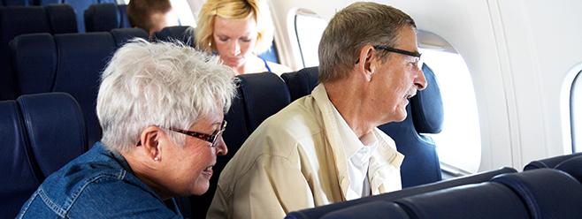 Älteres Paar, das im Flugzeug sitzt.
