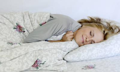 Schlaf - eine Frau liegt friedlich schlafend im Bett.