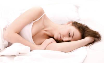 Schlaf-Tipps: eine Frau liegt friedlich schlafend im Bett.