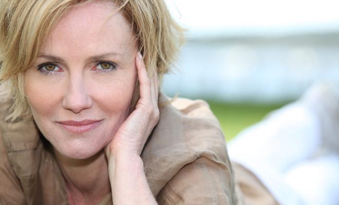 Haarausfall in der Menopause - eine Frau liegt im Gras