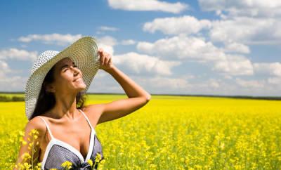 Sommerhitze: Eine Frau mit Sonnenhut steht auf einer Sommerwiese.