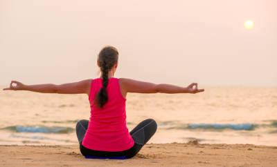 Bei Schmerzen im unteren Rücken hilft Bewegung. Eine Frau ist beim Training und fasst sich an den Rücken.