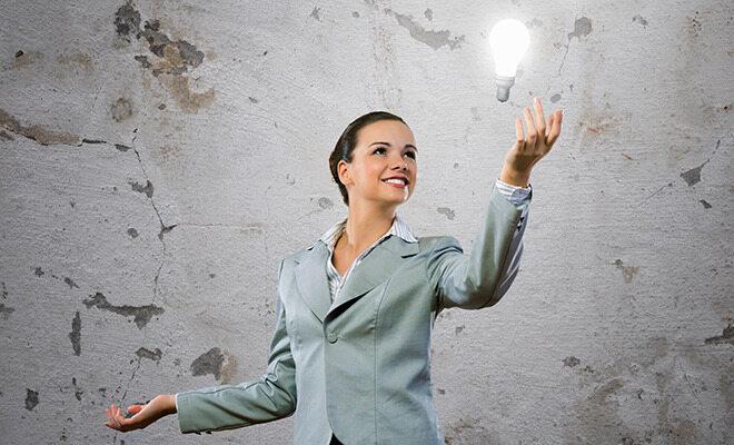 Frau im Kostüm hat eine Idee, symbolisiert durch eine Glühbirne
