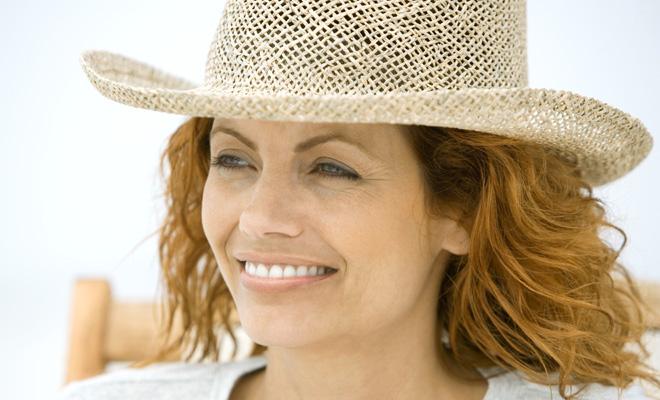Wechseljahre: eine Frau im besten Alter mit Strohhut