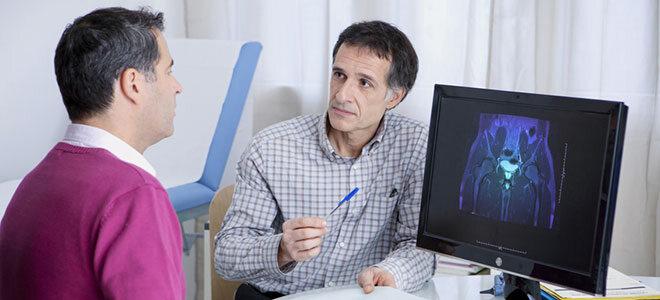 Arzt erklärt Patienten etwas anhand eines MRTs, auf dem die Prostata zu sehen ist.