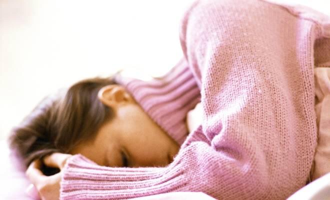 Stimmungsschwankungen bei Fibromyalgie? Eine Frau liegt auf dem Bett.