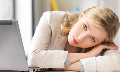 Fibromyalgie und Stress: Eine hübsche, müde Frau blickt in die Kamera.