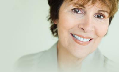 Fibromyalgie: Eine Frau lächelt in die Kamera.