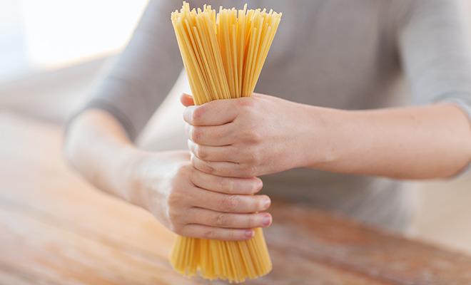 Frau hält ein Bund Spaghetti mit Gluten