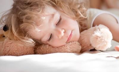 Kind kuschelt mit Teddy