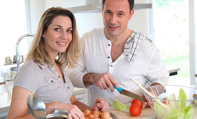 Abnehmen ohne Hungern: Ein Paar kocht mit frischem Gemüse.