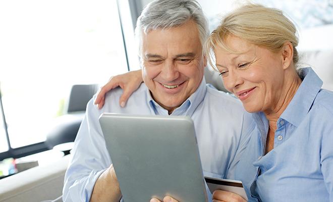 Älteres Paar macht Gehirnjogging mit Hilfe eines Tablets.
