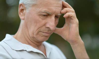 Mann mit Parkinson fasst sich an die Schläfe
