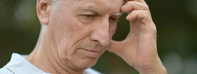 Mann mit Parkinson fasst sich an den Kopf