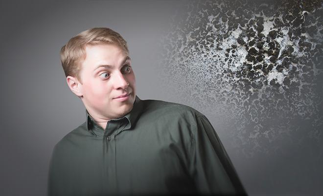 Mann blickt auf mit Schimmel befallene Wand