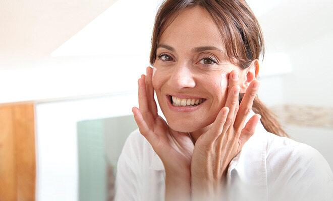 Vitamine für die Haut: Frau trägt Hautpflegecreme auf.
