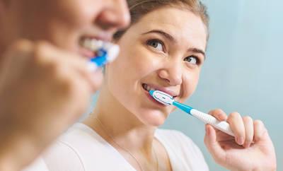 Frau putzt ihre Zähne mit Zahnbürste