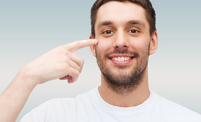 Augenzucken: Mann deutet auf sein Auge