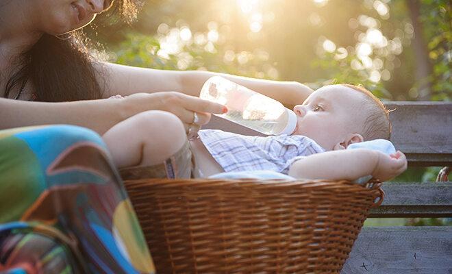 Frau füttert Baby im Park