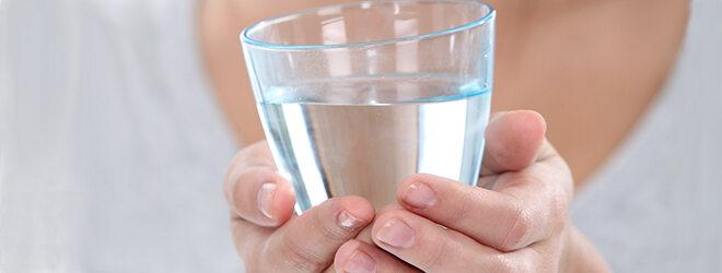 Detail: Frau hält ein Glas Wasser