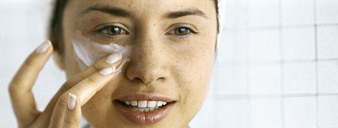 Junge Frau cremt Haut unter dem Augen ein
