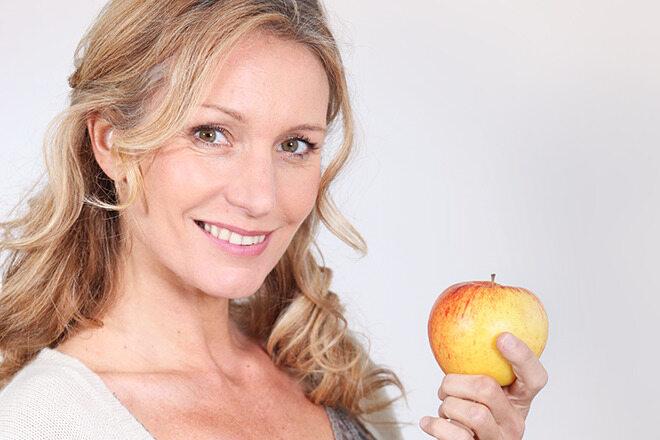 Vitamine für die Haare: Eine Frau hält einen Apfel