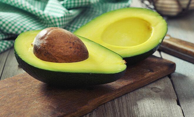 Aufgeschnittene Avocado auf einem Holzbrett