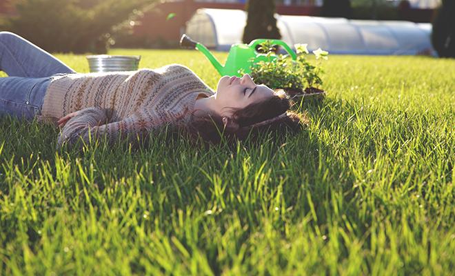 Junge Frau liegt im Garten auf einer Wiese und schläft