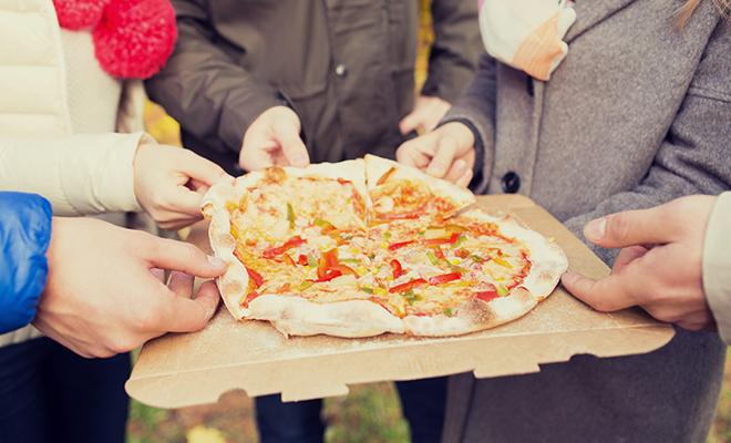 Jugendliche teilen sich eine Pizza