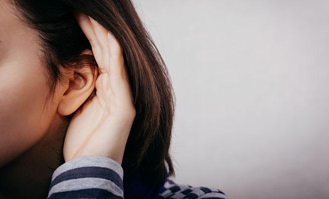 Mädchen fasst sich ans Ohr und will Ohren reinigen (Detail)