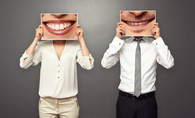 Frau und Mann halten Bildern mit großem Lächeln vor ihre Gesichter