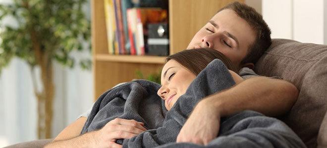 Junges Paar, das zusammen auf Sofa kuschelt.
