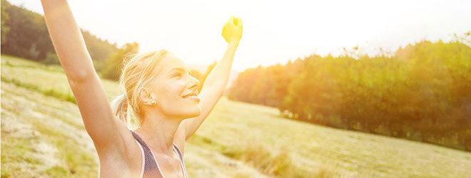 Frau hebt beim Laufen die Arme.