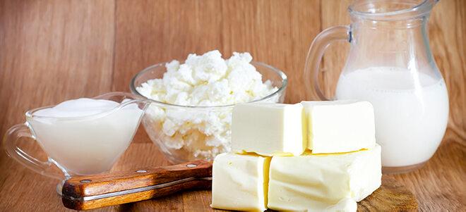 Verschiedene Milchprodukte, die auf einem Holzhintergrund schön angerichtet sind.