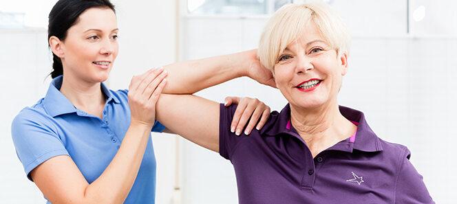 Ältere Frau, die bei Krankengymnastik ihre Schulter bewegt.
