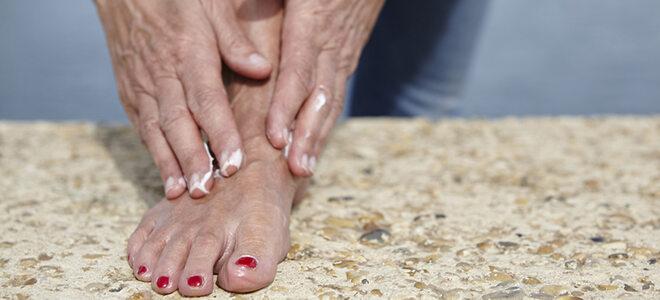 Ältere Frau, die ihre Füße eincremt, um Hühneraugen vorzubeugen.