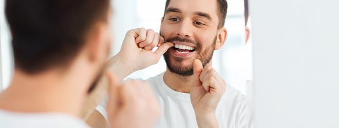 Mann benutzt Zahnseide gegen Zahnfleischentzündung