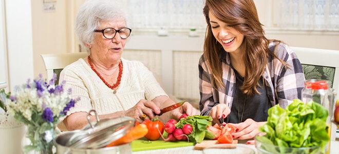 Seniorin und junge Frau, die gemeinsam Gemüse schneiden.
