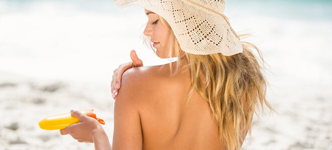 Frau, die sich die Schultern mit Sonnencreme eincremt.