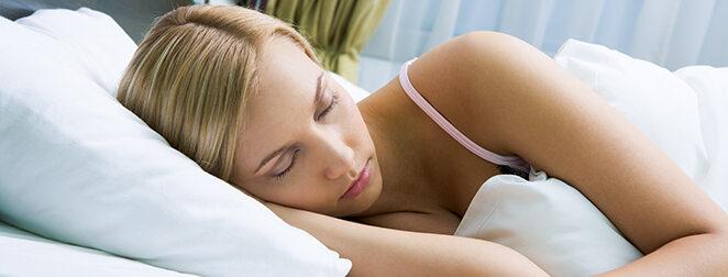 Junge Frau, die auf Bett liegt und schläft.