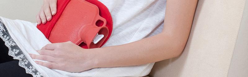 Probiotika: Frau mit Wärmflasche