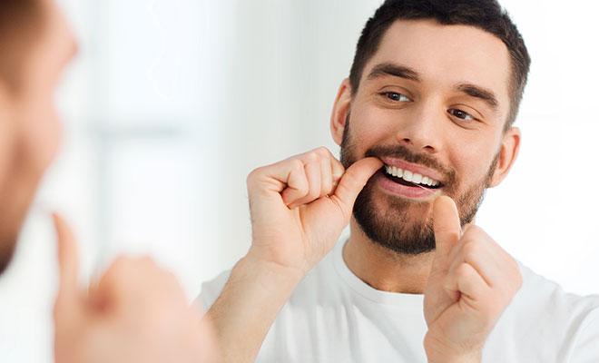 Zahnseide benutzen: Mann reinigt seine Zähne