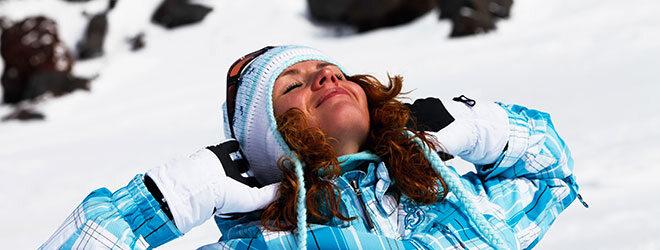 Frau steht draußen im Winter in der Sonne und sonnt sich.