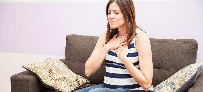 Schwangere Frau, die sich an die Brust langt.